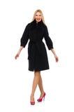 Recht blonde Frau im schwarzen Mantel lokalisiert auf Weiß Stockfotografie