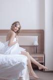 Recht blonde Frau im Tuch sitzen auf Bett Stockbild