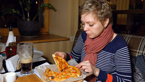 Recht blonde Frau isst Pizza und trinkt Bier Stockfotografie