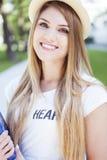 Recht blonde Frau mit dem Hut, der ein Buch hält Lizenzfreies Stockfoto