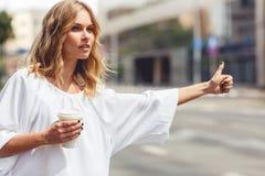 Recht blonde Frau mit dem Kaffee, der Transport stoppt Lizenzfreie Stockfotos