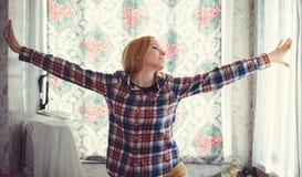 Recht blonde Frau mit dem langen Haar, ein schönes Porträt im Haus freut sich Hände auf den Seiten, ein einfaches Bild eines Haus Stockfotografie