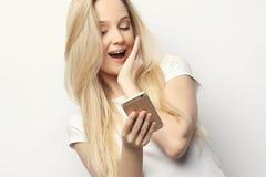 Recht blonde Frau mit dem langen Haar hält modernes intelligentes Telefon, empfängt unexpcted Mitteilung vom Freund, liest Anzeig Stockbilder