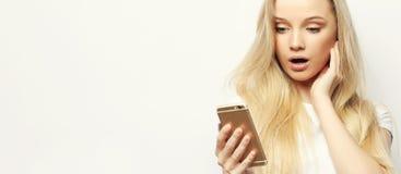 Recht blonde Frau mit dem langen Haar hält modernes intelligentes Telefon, empfängt unexpcted Mitteilung vom Freund, liest Anzeig Stockfoto