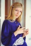 Recht blonde Frau mit dem umsponnenen Haar, gekleidet in einem blauen Kleid, schönes Porträt im Haus, einfaches Hauptbild, Haarpf Lizenzfreies Stockfoto