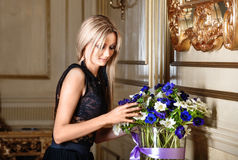 Recht blonde Frau mit den Blumen, zuhause Lizenzfreie Stockbilder