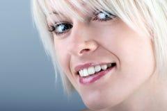 Recht blonde Frau mit einem schönen Lächeln Stockfotografie
