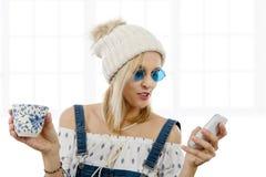 Recht blonde Frau mit einer Tasse Tee und Telefon Stockbild