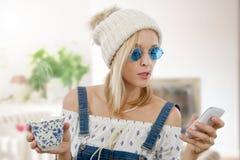 Recht blonde Frau mit einer Tasse Tee und Telefon Stockfotografie
