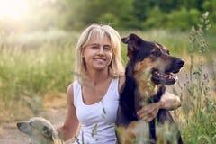 Recht blonde Frau mit ihren zwei Hunden Stockbilder