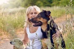 Recht blonde Frau mit ihren zwei Hunden Lizenzfreie Stockfotos