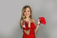 Recht blonde Frau mit Schuhen bauschen sich in den Händen Lizenzfreies Stockfoto