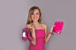 Recht blonde Frau mit Schuhen und Tasche in den Händen Lizenzfreies Stockbild