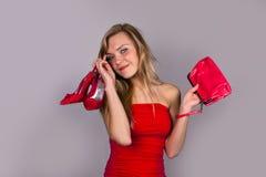 Recht blonde Frau mit Schuhen und Tasche in den Händen Lizenzfreie Stockfotos