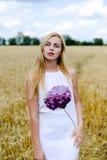 Recht blonde Frau mitten in gelbem Weizen Stockfotos