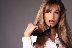 Recht blonde Frauenholdingsonnenbrillen Stockbild