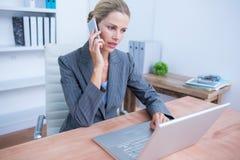 Recht blonde Geschäftsfrau, die ihren Laptop anruft und verwendet Lizenzfreies Stockfoto