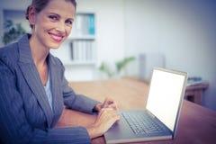 Recht blonde Geschäftsfrau, die ihren Laptop verwendet Stockfoto