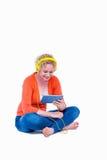 Recht blonde hörende Musik mit ihrem Tablet-Computer Stockfoto