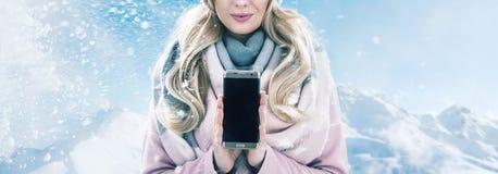 Recht blonde Holding ein Smartphone, Winterwetter Lizenzfreies Stockbild