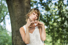 Recht blonde junge Frau, die Herzzeichen mit tut Stockbild