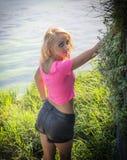 Recht blonde junge Frau im Freien mit Wasser und Anlagen hinten Lizenzfreies Stockbild