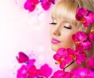 Recht blonde junge Frau mit Blumen Lizenzfreie Stockfotos