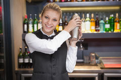 Recht blonde Kellnerin, die Cocktail rüttelt Stockfotografie