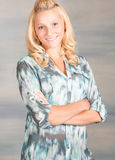 Recht blonde lächelnde Frau im blauen Hemd Stockfotografie
