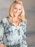 Recht blonde lächelnde Frau im blauen Hemd Lizenzfreie Stockfotografie