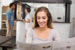 Recht blonde Lesung die Zeitung Stockfoto