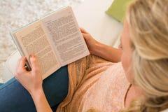 Recht blonde Lesung ein Buch, das auf der Couch sitzt Stockbild