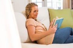 Recht blonde Lesung ein Buch, das auf der Couch sitzt Lizenzfreie Stockfotos
