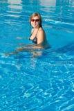 Recht blonde Mädchenschwimmen im Pool Stockfotos