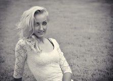 Recht blonde Niederlegung der jungen Frau im Freien auf Gras Stockfoto