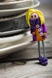 Recht blonde Puppe kleidete in Purpurrotem und in Orange an stockbild