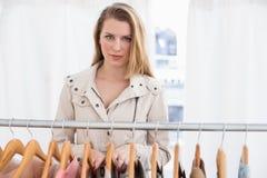 Recht blonde schauende Kamera durch Kleidungsschiene Stockfoto