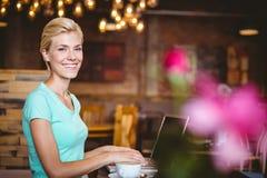 Recht blonde schauende Kamera und Anwendung der Laptop-Computers Lizenzfreie Stockbilder