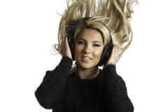 Recht blonde schleudernde Haar-hörende Kopfhörer lokalisierten Hintergrund Lizenzfreie Stockfotos