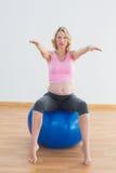 Recht blonde schwangere Frau, die auf Übungsball sitzt Stockbild