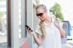 Recht blonde simsende und haltene Einkaufstaschen Stockfotografie
