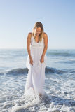 Recht blonde Stellung im Meer am Strand in den weißen sundress Stockbild
