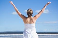 Recht blonde Stellung mit den Armen streckte auf dem Strand aus Lizenzfreies Stockfoto