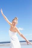 Recht blonde Stellung mit den Armen streckte auf dem Strand aus Stockbilder