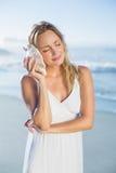 Recht blonde Stellung am Strand in den weißen sundress, die auf Tritonshorn hören Stockfotografie