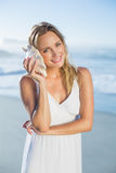 Recht blonde Stellung am Strand in den weißen sundress, die auf Tritonshorn hören Stockfoto