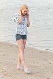 Recht blonde Unterhaltung auf Mobiltelefon und Lächeln Stockbild