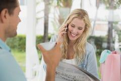 Recht blonde Unterhaltung am Telefon beim Trinken des Kaffees mit Freund Stockbilder