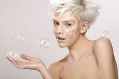 Recht blonde vorbildliche Spiele mit Seifenblasen Stockfotografie