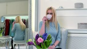 Recht blonde weibliche Entspannung mit dem Kaffee, der nahe dem Spiegel in der Luxusboutique sitzt stock video footage